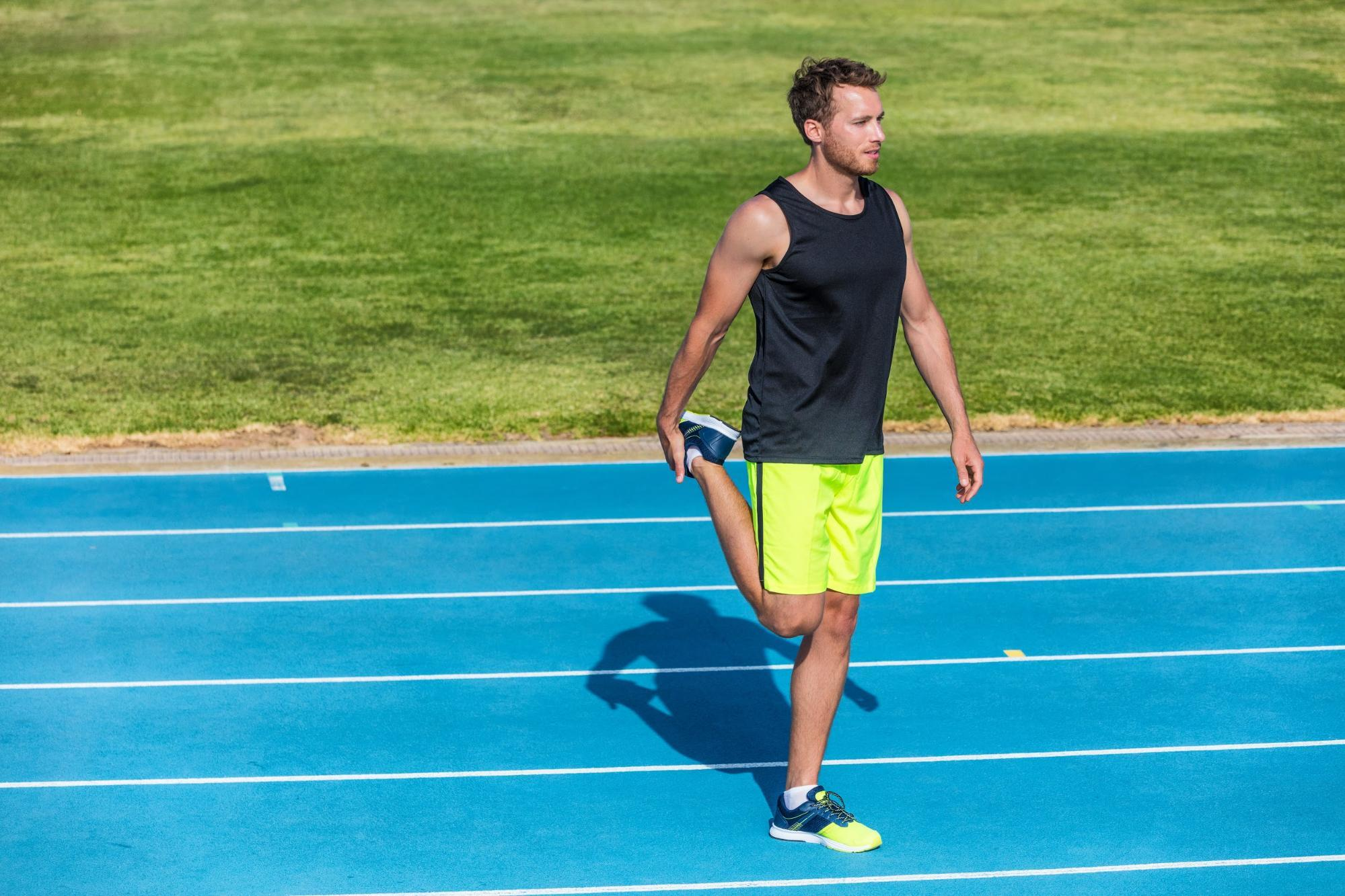 male stretching leg on running track