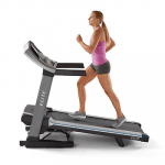 A fit woman in athletic attire running on the Horizon T9-02 Treadmill on an incline