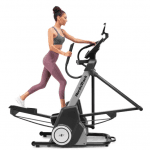 A fit woman in athletic attire working out on the FS5i Freestride Trainer
