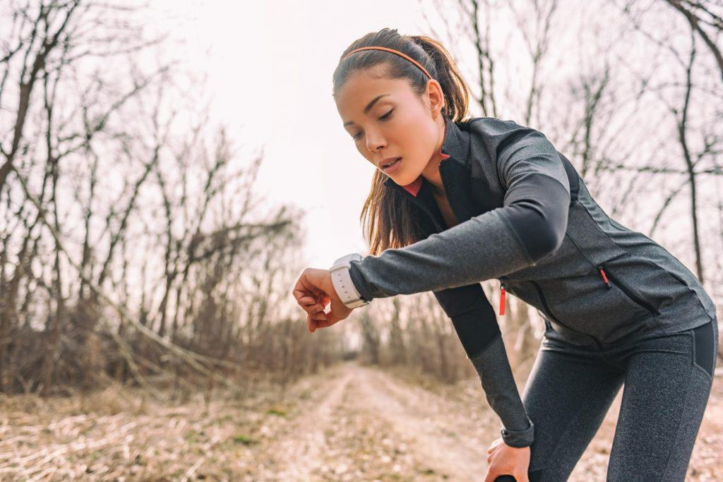 a female runner bent down looking at her watch
