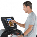 A fit man in athletic attire walking on the Landice L8 Treadmill setting up his workout on the screen