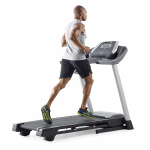 A fit man in athletic attire running on the ProForm 505 CST treadmill