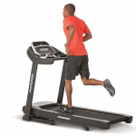 A fit man in athletic attire running on the Horizon Adventure 5 Treadmill