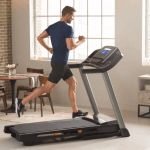 A fit man in athletic attire running on the T 6.5 Si treadmill in a living room setting with 2 big windows, a table, shelves and chairs