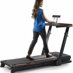A woman in business casual attire walking on the Nordictrack Treadmill desk while working on a laptop