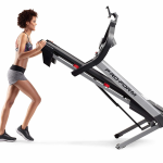 A woman in athletic attire folding the ProForm Smart Performance 600i Treadmill