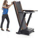 A woman wearing business work attire folding the Nordictrack Treadmill Desk