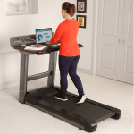 A woman in athletic attire walking on the Life Fitness Treadmill desk while working on a laptop in a bedroom setting