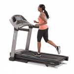 A fit woman in athletic attire running on the Horizon T7-02 Treadmill