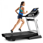 A woman in athletic attire runnig on the Smart Pro 5000 Treadmill
