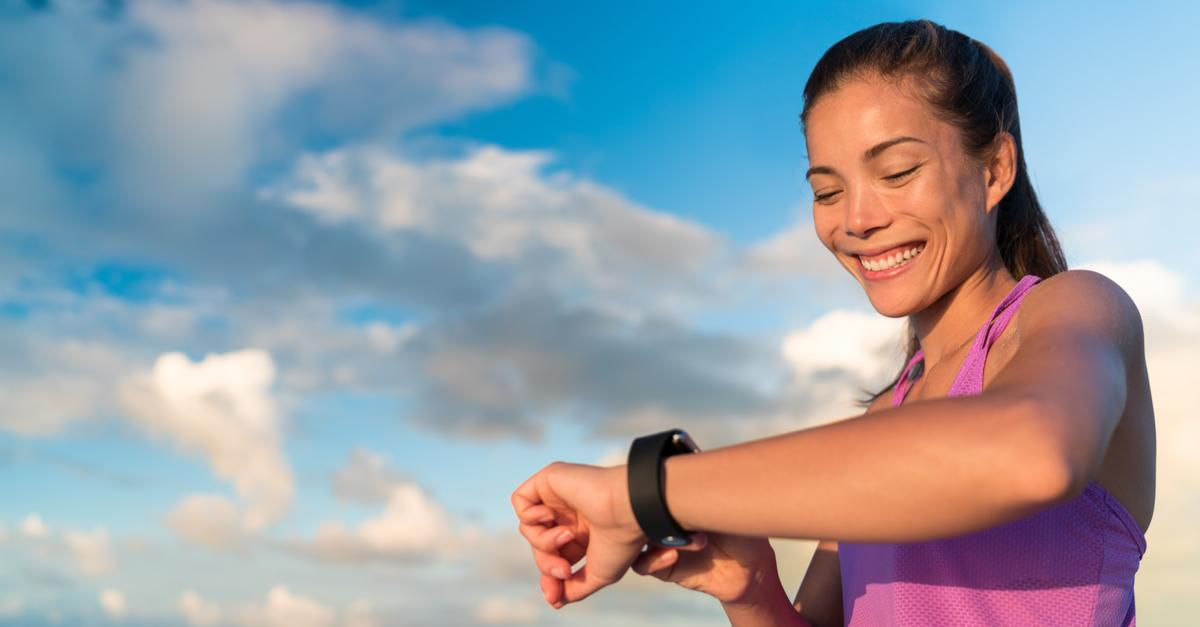 Woman checking fitness tracker on run